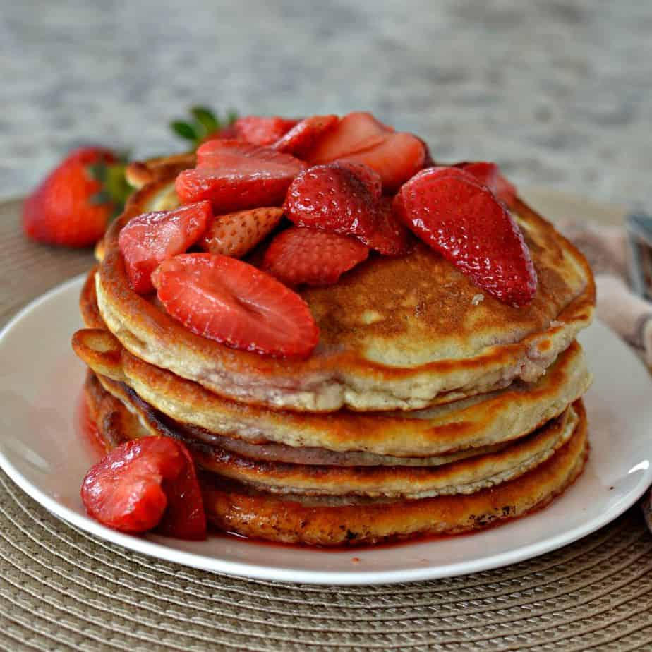 Light, fluffy, and golden pancakes topped with fresh strawberries and a sweet strawberry syrup