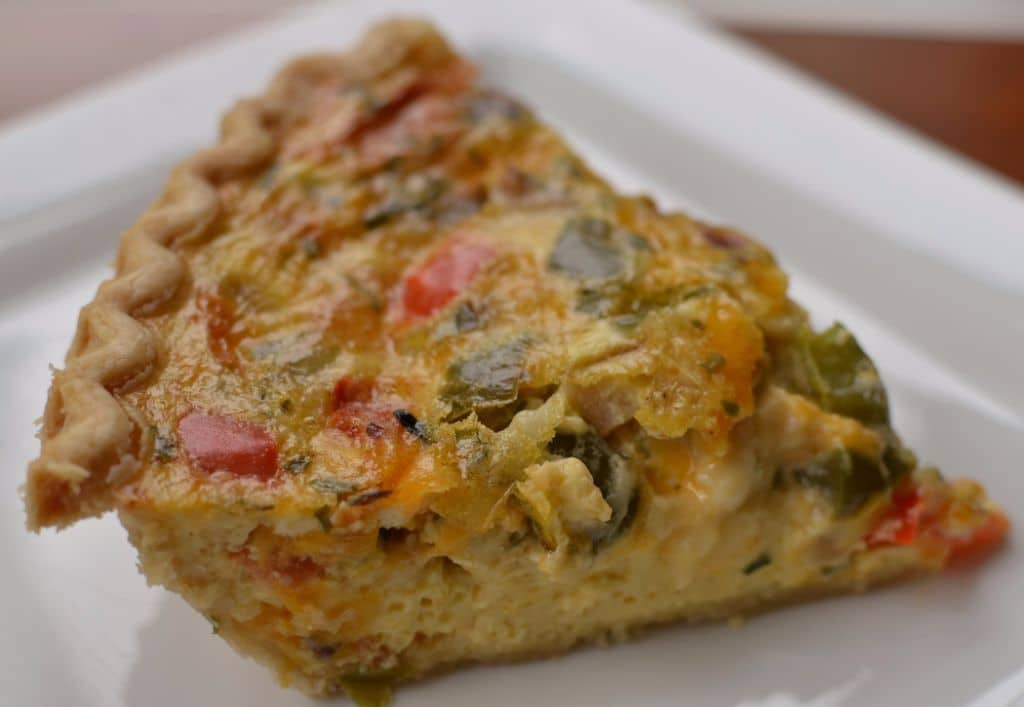 A light and delicious breakfast quiche filled with bacon, mushrooms, peppers, and tomatoes
