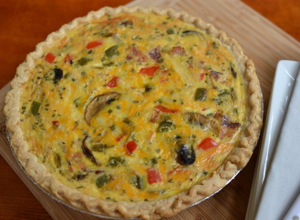 This easy weekend breakfast quiche is filled with bacon, mushrooms, peppers, and tomatoes