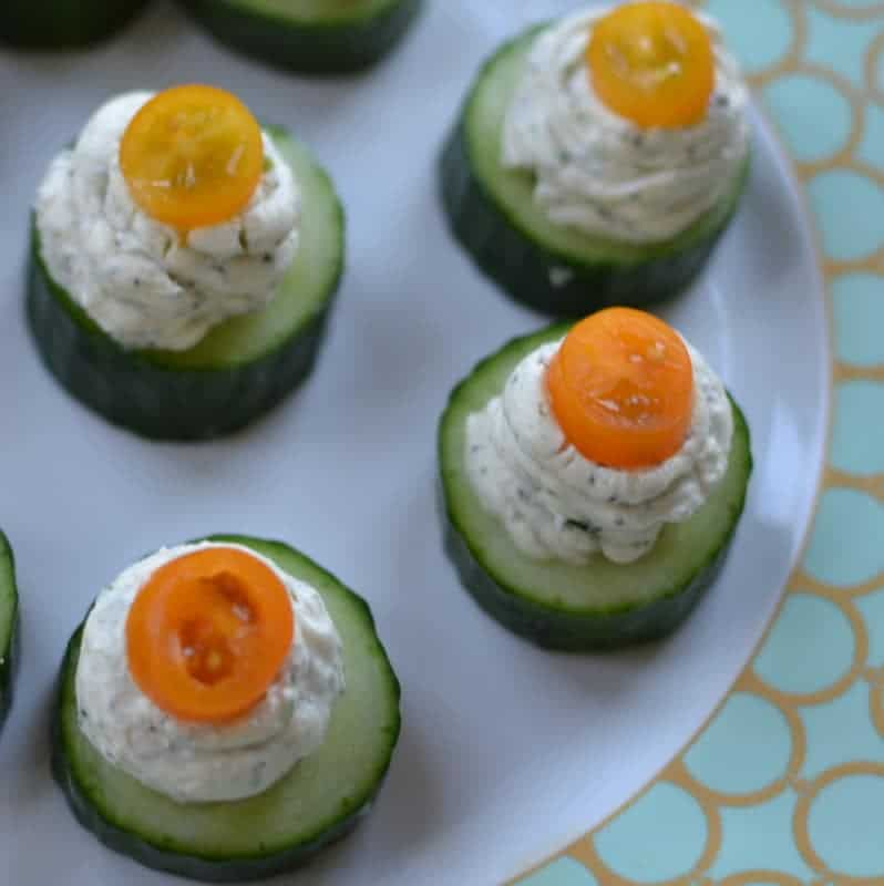 Herb cream cheese on small cucumber bites, topped with cherry tomato slices