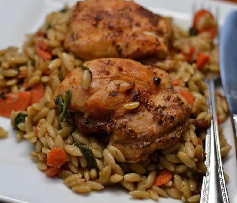 Perfectly seasoned chicken thighs atop a bed of tender orzo and vegetables