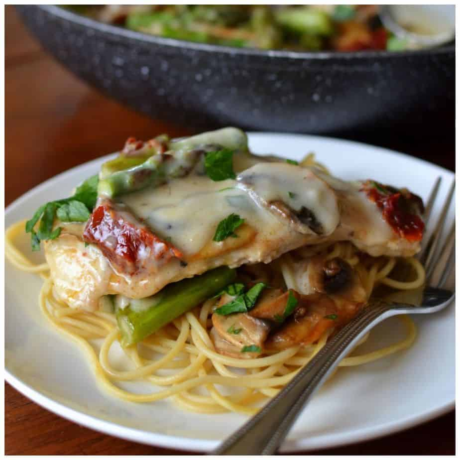 Serve this creamy mushroom chicken topped with tender asparagus and sun dried tomatoes over a bed a tender spaghetti
