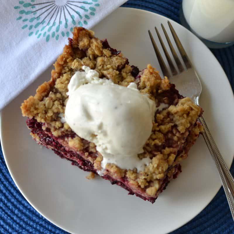 Sweet and tart blackberry crisp topped with vanilla bean ice cream