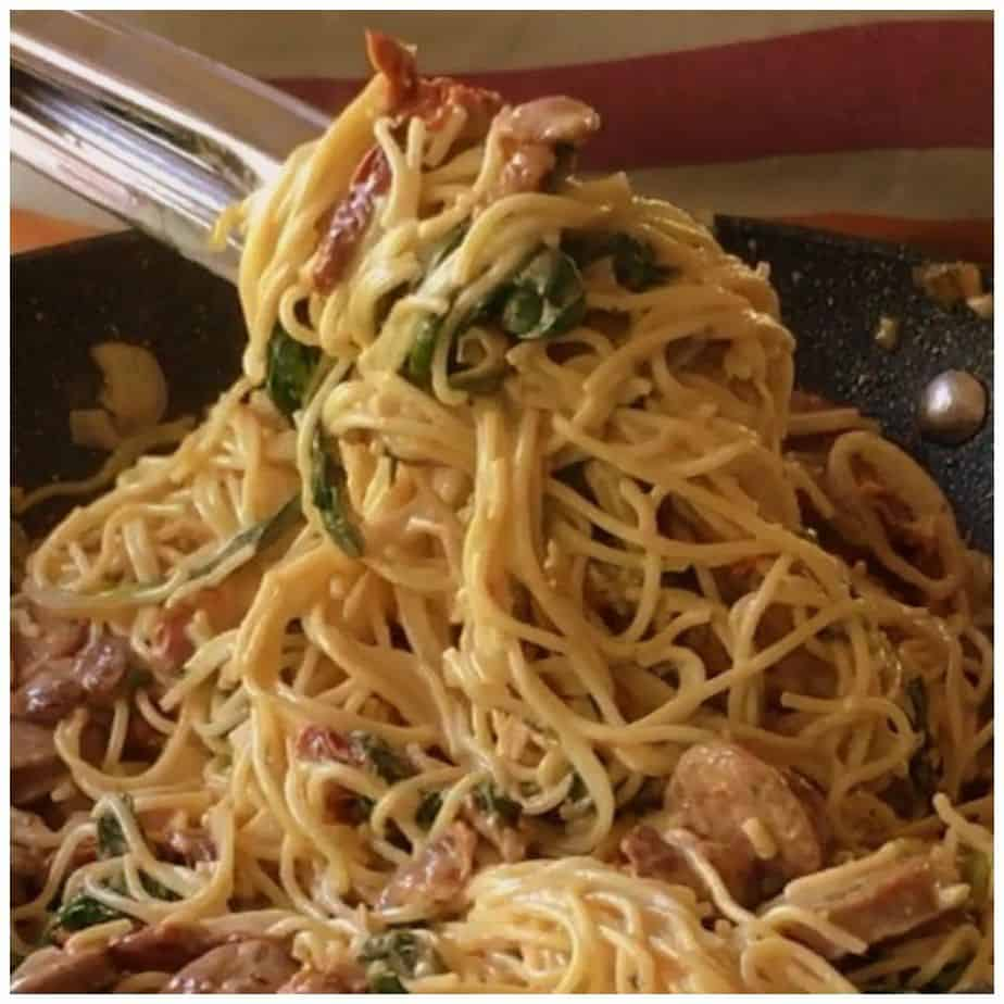 A deliciously creamy sun dried tomato and sausage pasta with bacon and spinach