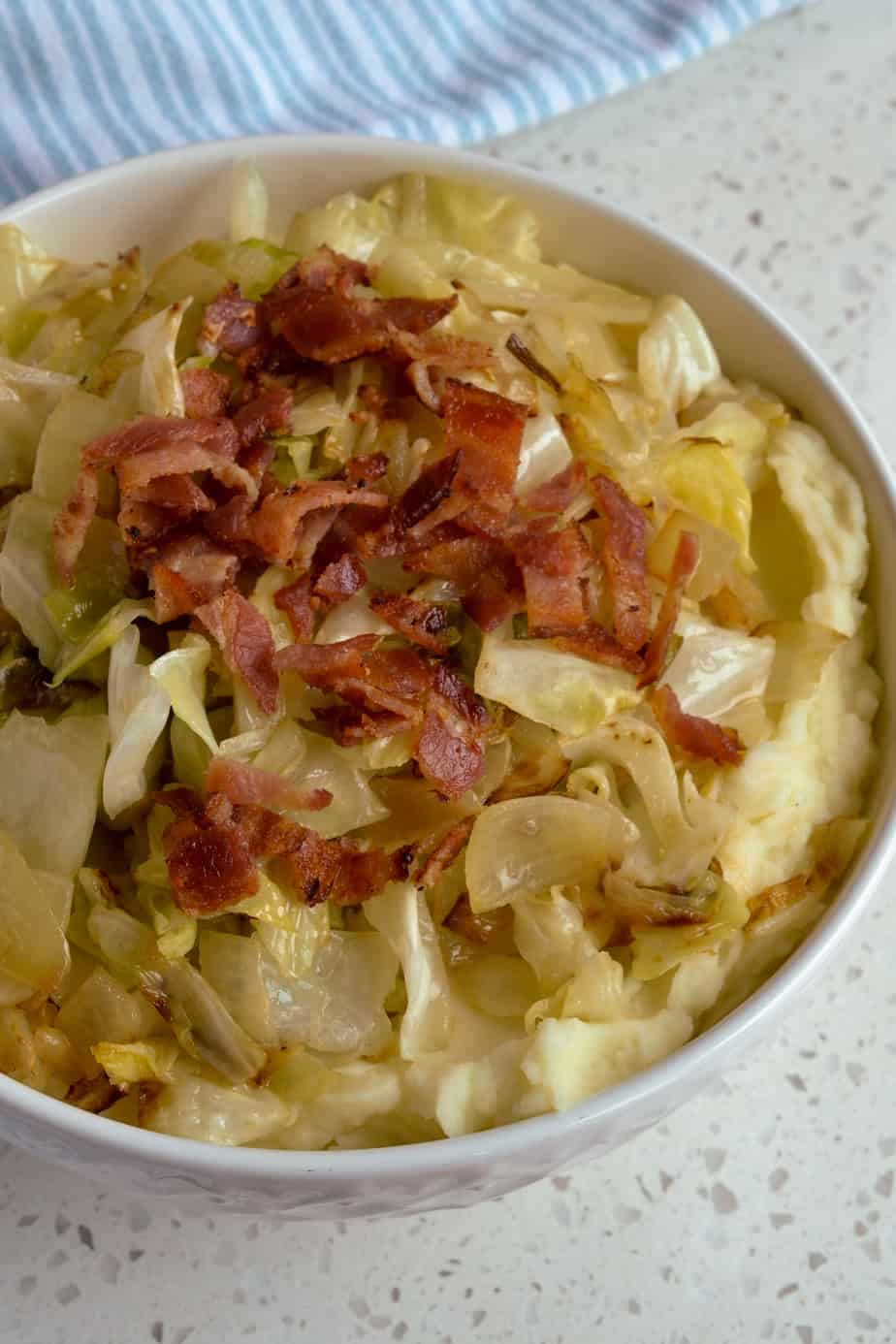 Irish Colcannon is made with mashed potatoes, fried cabbage, onions, crisp bacon and seasoned with salt and pepper.