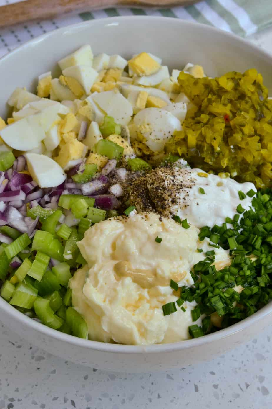 Potatoes, mayonnaise, mustard, celery, red onion, hard boiled eggs, pickle relish and chives in a bowl.