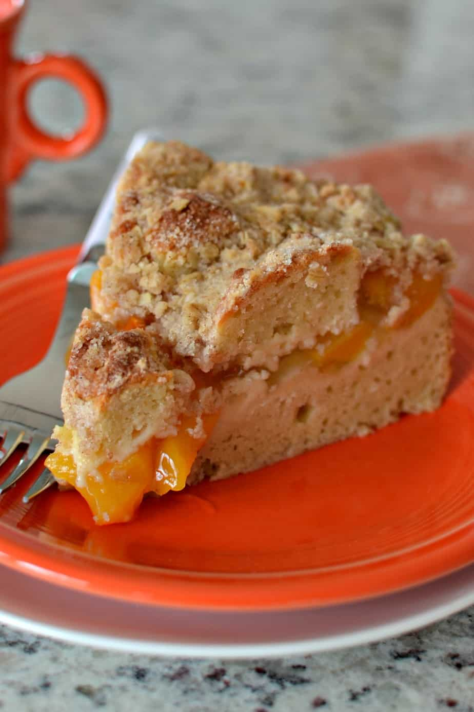 A family friendly sweet peach coffee cake with a sour cream base and a crunchy oatmeal crumb topping
