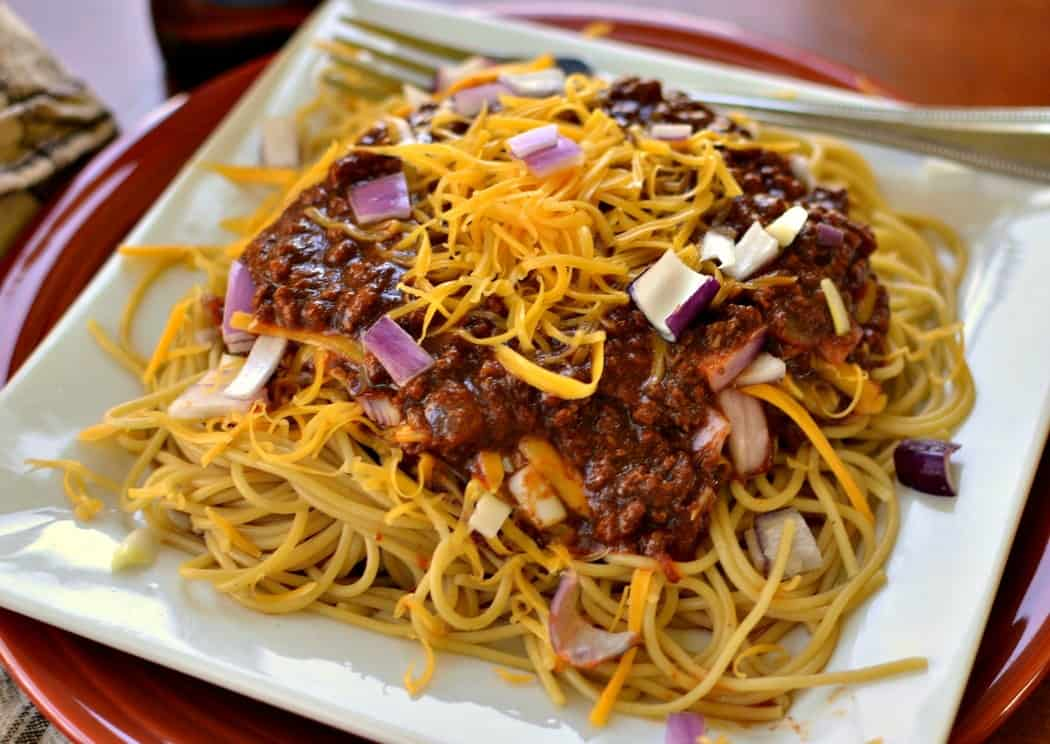 Cincinnati Chili is traditionally served over spaghetti noodles with shredded cheddar and onions.