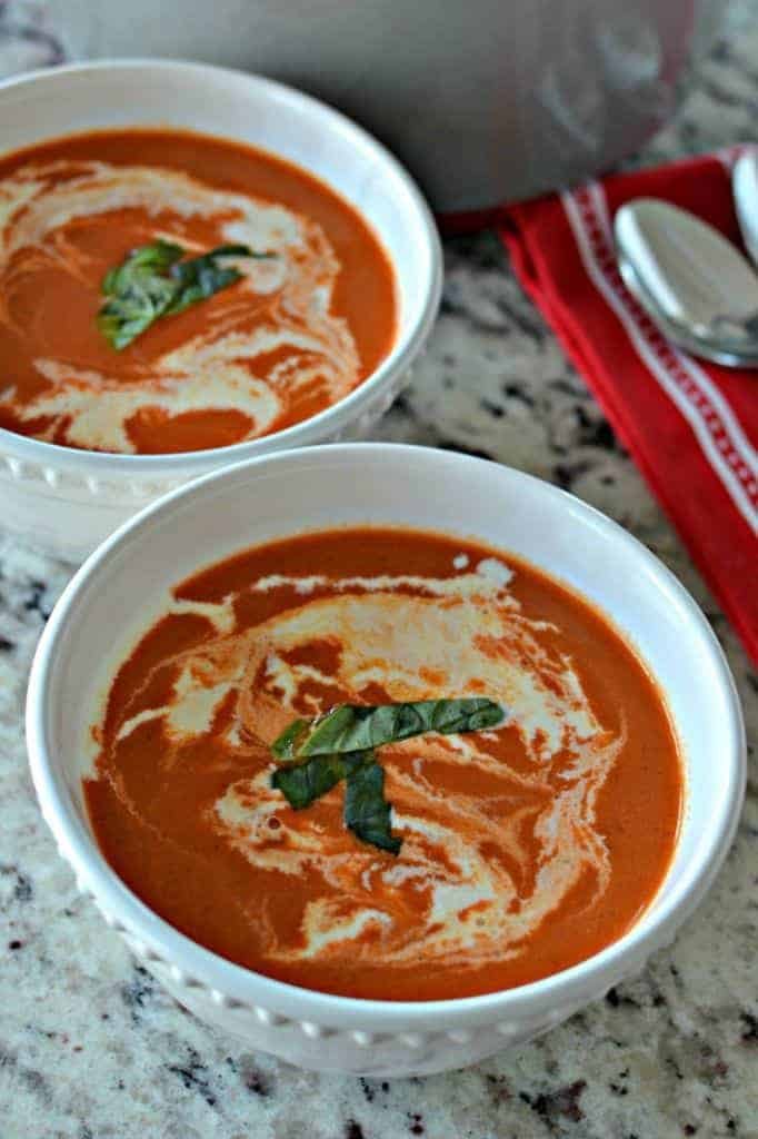 Drizzled with cream and topped with a ribbon of basil, this homemade tomato bisque soup is a creamy, delicious meal