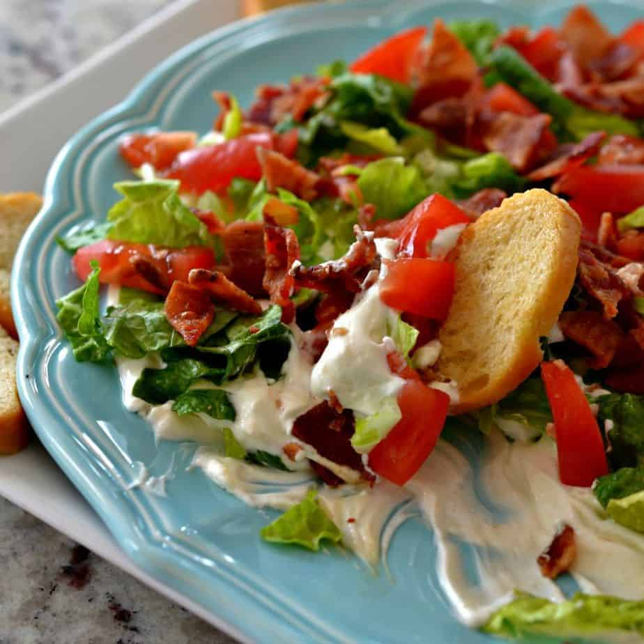 A creamy cream cheese base is layered with lettuce, bacon, and tomato