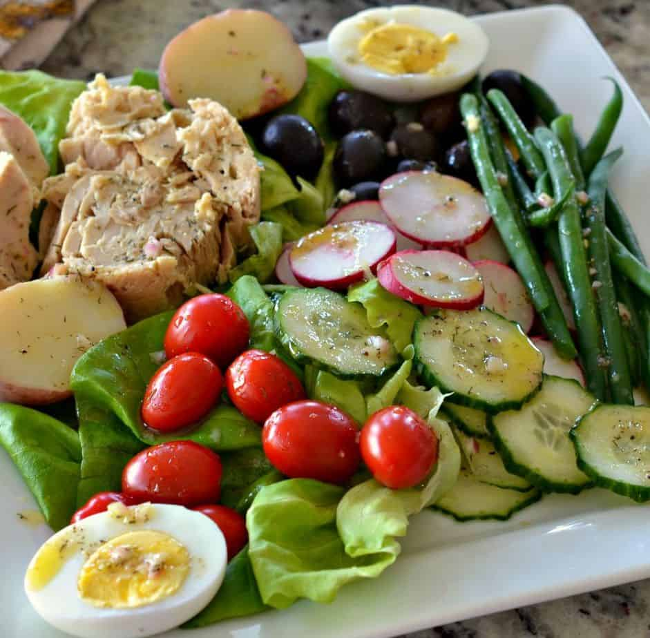 A salad of fresh vegetables, red potatoes, eggs, olives and tuna drizzled with a tangy light mustard vinaigrette.