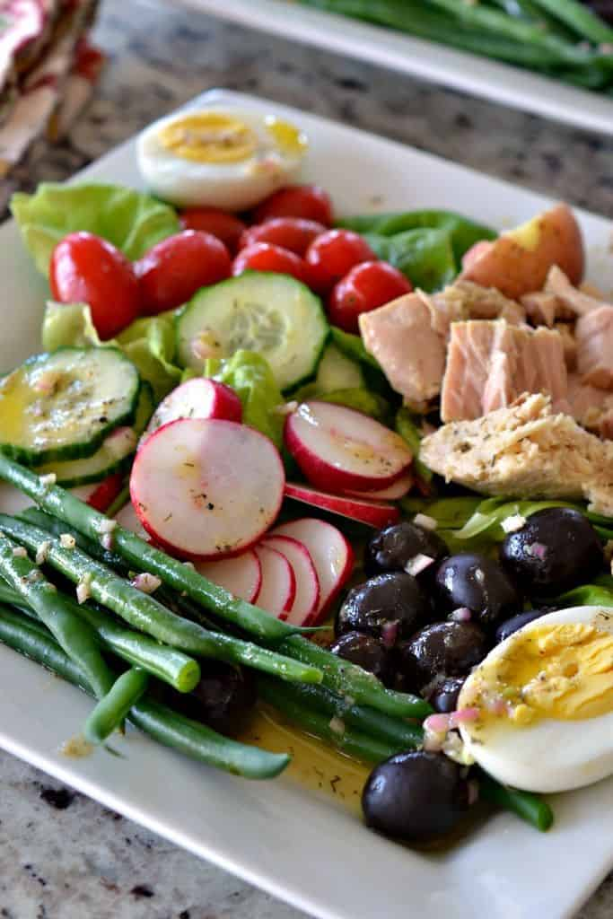 A salad of fresh vegetables, red potatoes, eggs, olives and tuna drizzled with an easy six ingredient mustard vinaigrette.