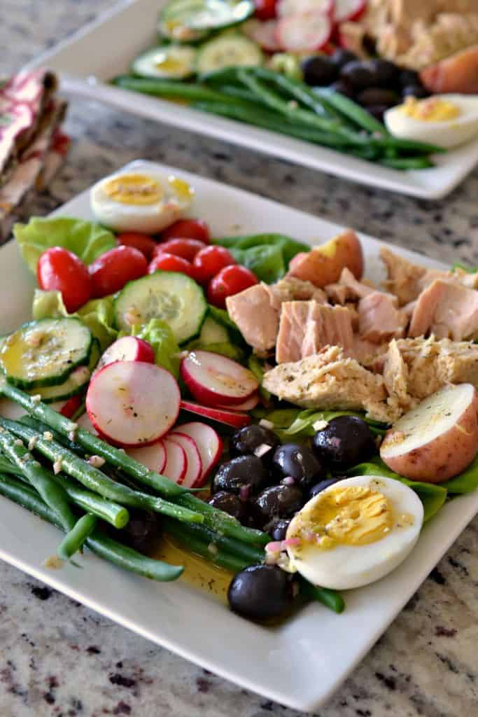 Nicoise Salad is a salad with vegetables, Nicoise olives, red potatoes, hard boiled eggs and tuna with mustard vinaigrette.