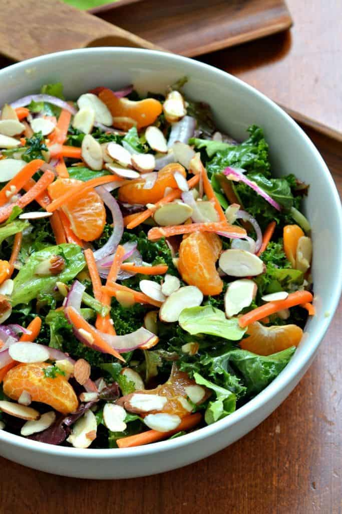 Topped with mandarin oranges, carrots, almonds, and a zesty ginger Vinaigrette, this kale salad is fresh and delicious