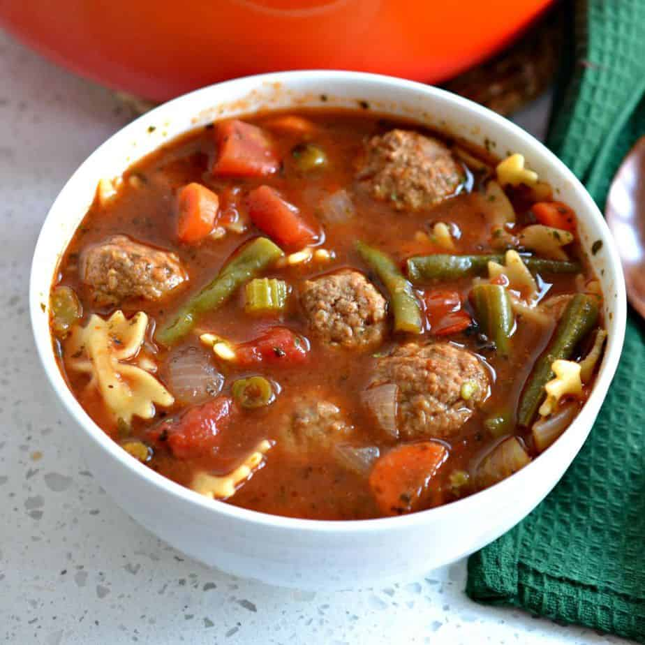 Soup with meatballs, carrots, celery, tomato and green beans.