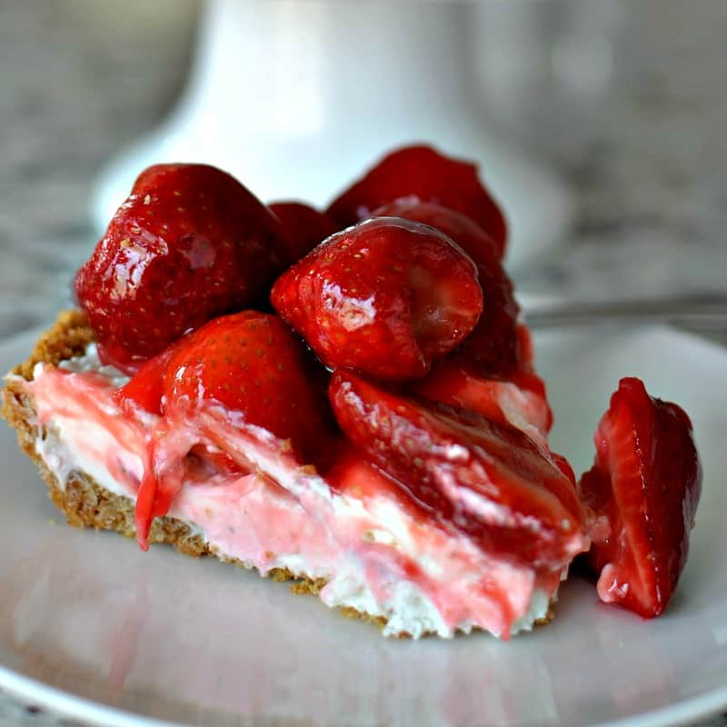 A slice of cream cheese pie with fresh strawberries on it.