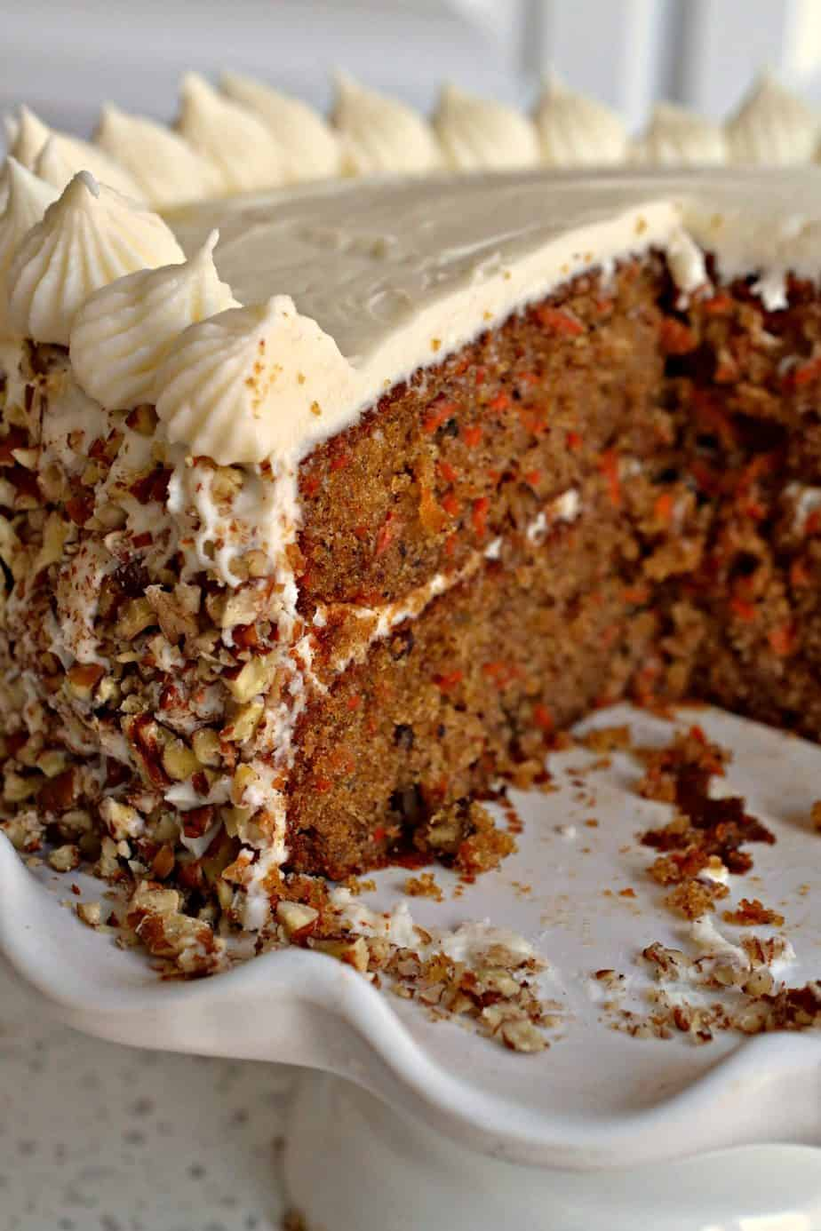 A delectable moist holiday carrot cake with a silky cream cheese frosting with chopped pecans.