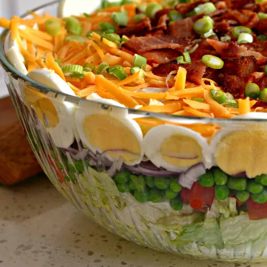 This tasty Seven Layer Salad is a real crowd pleaser with tomatoes, peas, hard boiled eggs, crisp bacon and sharp cheddar.