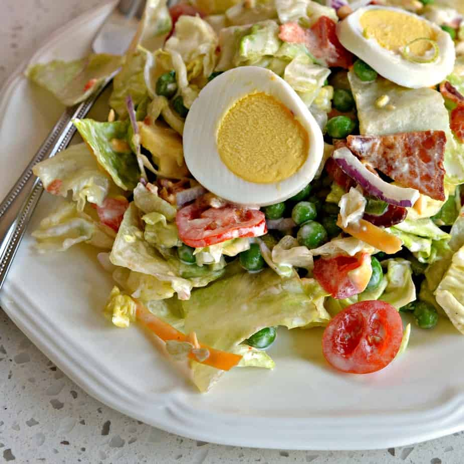 Seven Layer Salad is tasty salad with peas, bacon, hard boiled eggs and cheddar cheese.