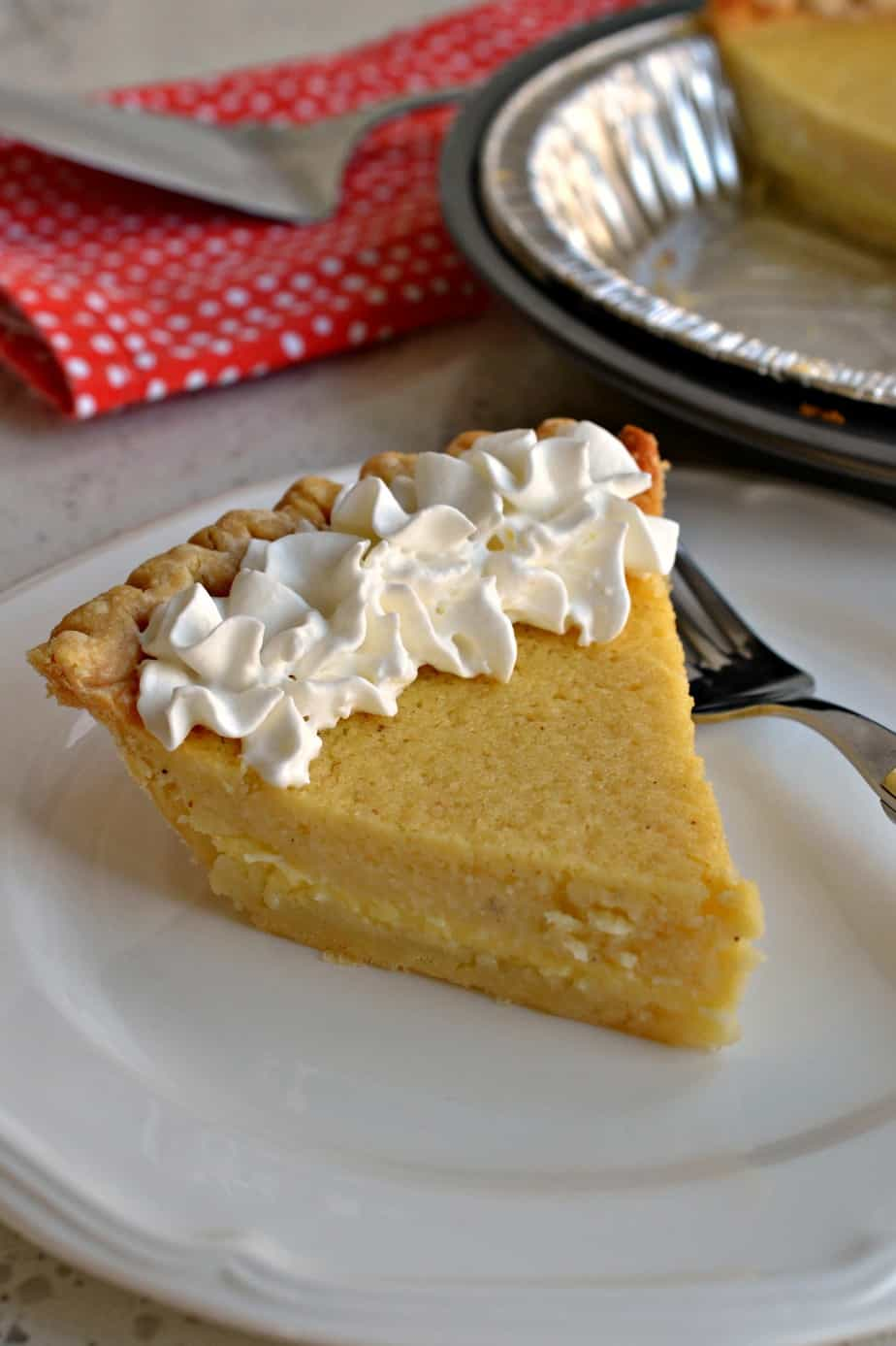 A delicious slice of buttermilk pie topped with fresh whipped cream is the perfect dessert