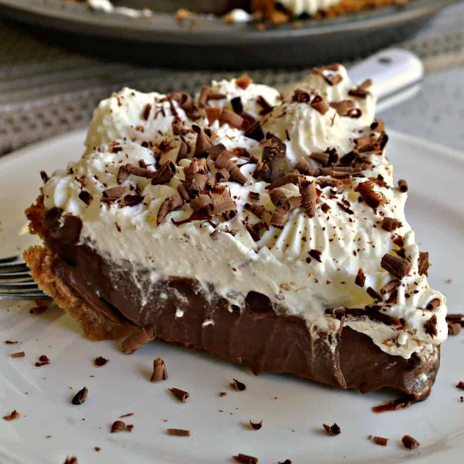 A decadently rich chocolate pie nestled in a graham cracker crust garnished with fresh whipped cream and chocolate shavings.