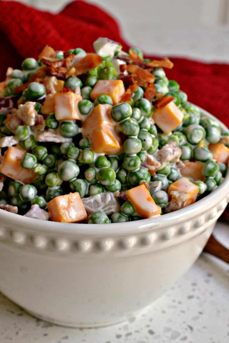 Creamy Pea Salad combines sweet peas, crispy bacon, red onion and cheddar cheese in a creamy five ingredient dressing.