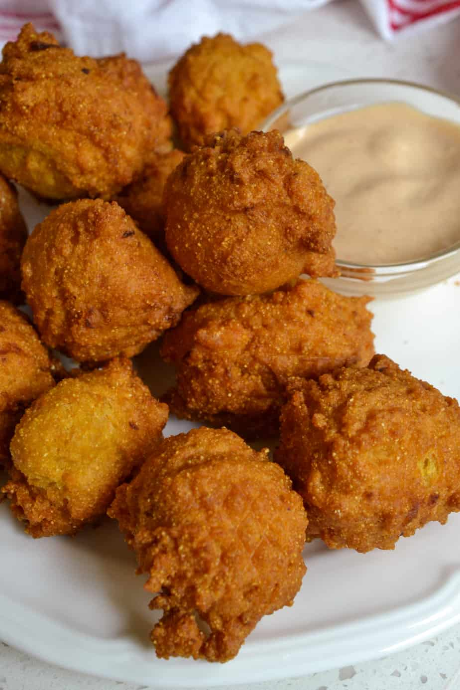 Warm and crispy fried hush puppies with a spicy southern sauce