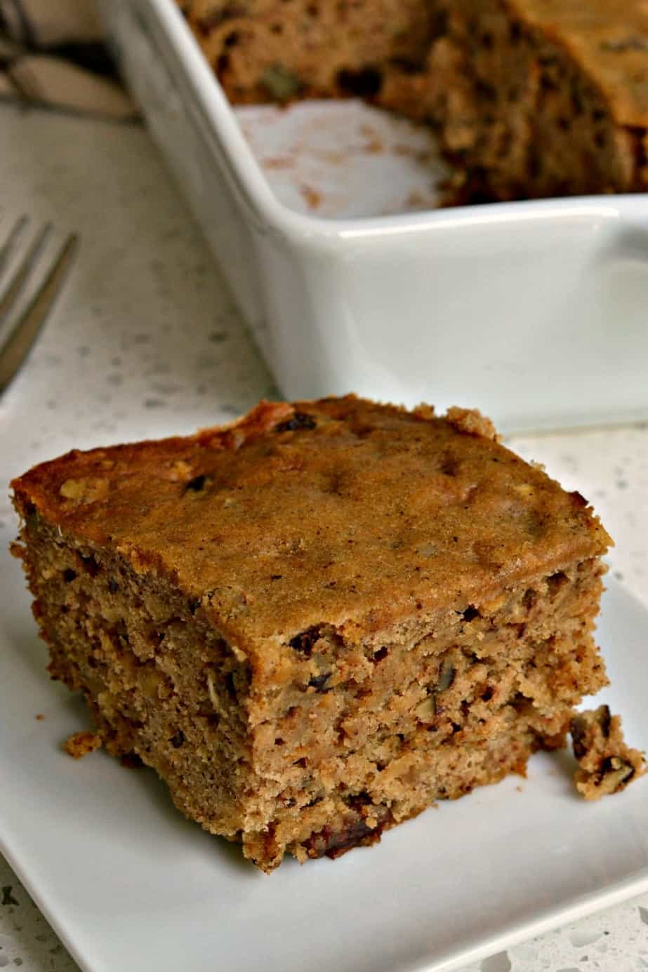 An easy family friendly scrumptiously moist applesauce spice cake with pecans and raisins.