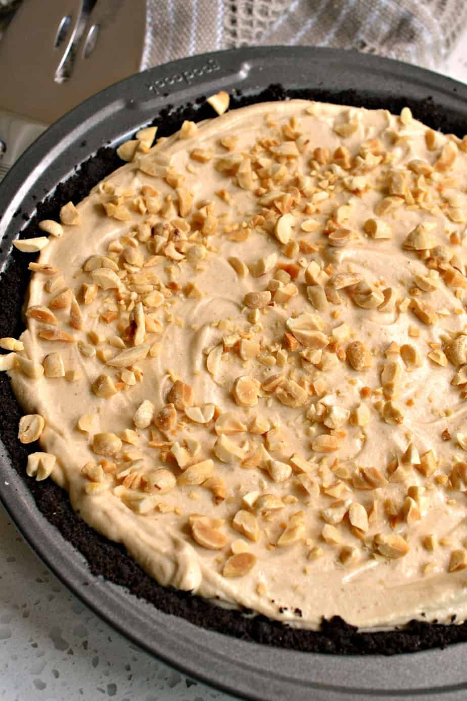 This easy no bake Peanut Butter Pie is topped with chopped peanuts, chocolate and butterscotch sauce.