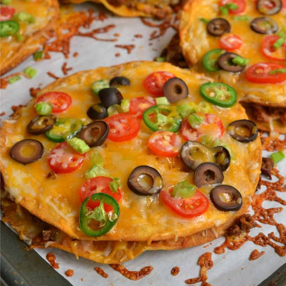 These Mexican pizzas are double decker crispy fried tortilla pizzas stuffed with seasoned beef, refried beans, and cheese.