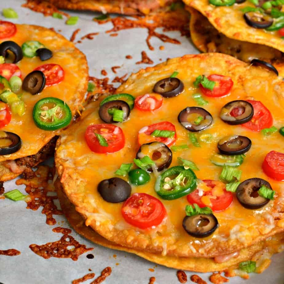 Mexican Pizzas stuffed with refried beans and taco seasoned ground beef then topped with oodles of cheese and tomatoes.