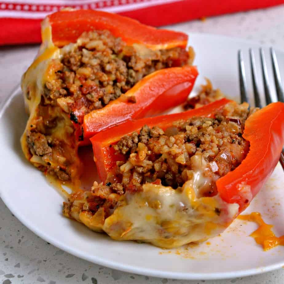These festive, fun, and easy Mexican Stuffed Peppers are loaded with seasoned ground beef, onions, tomatoes and rice,.