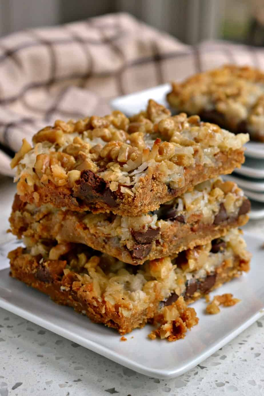Scrumptious Magic Cookie Bars are loaded with chocolate chips, peanut butter chips, coconut, and walnuts.