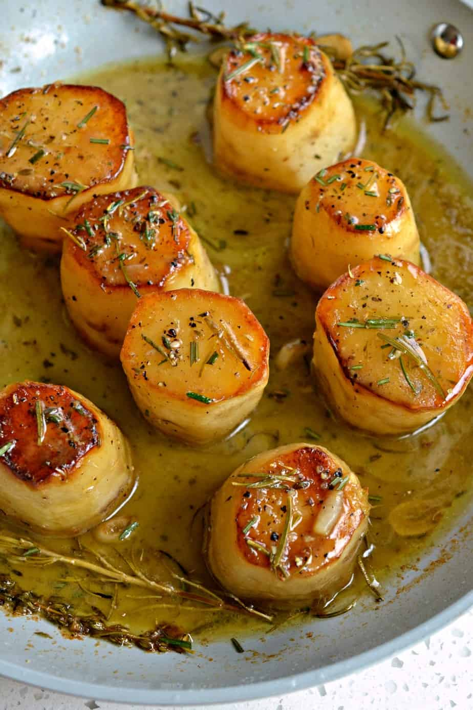 Elegant Fondant Potatoes are browned and then baked in creamy butter and rich chicken stock with aromatic fresh herbs.