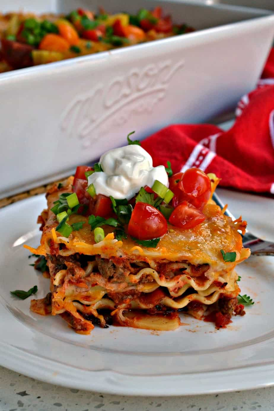 This Mexican Lasagna has layers of melted cheese, taco seasoned ground beef, and creamy refried beans.