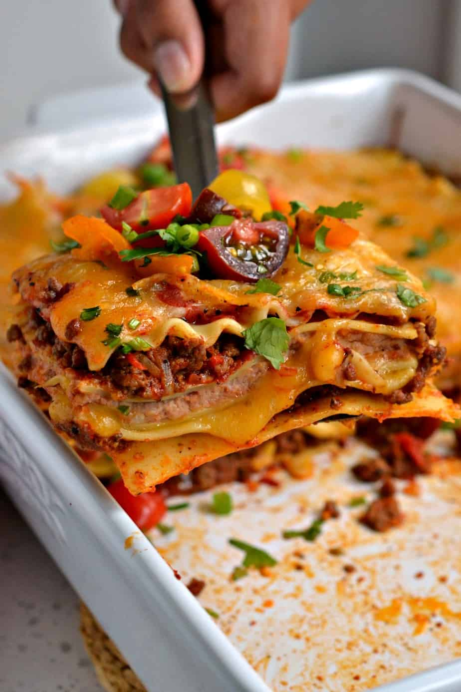 Mexican Lasagna is a hearty meal with an abundance of flavors from taco seasoned ground beef, onions, and refried beans.