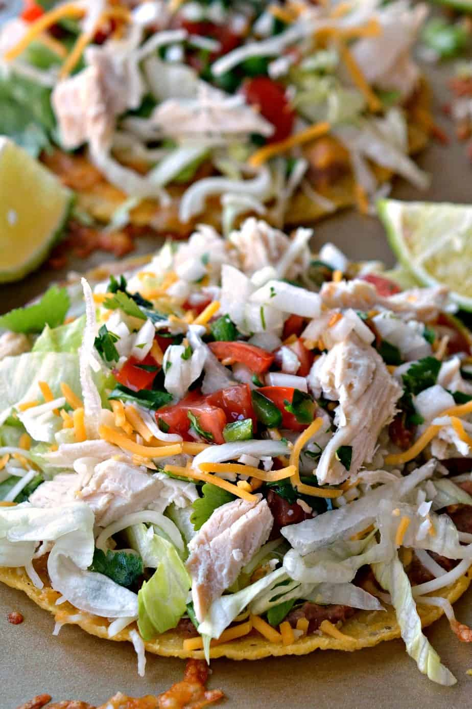 Fun and Easy Tex Mex Chicken Tostadas made with homemade pico de gallo, rotisserie chicken, and plenty cheese.