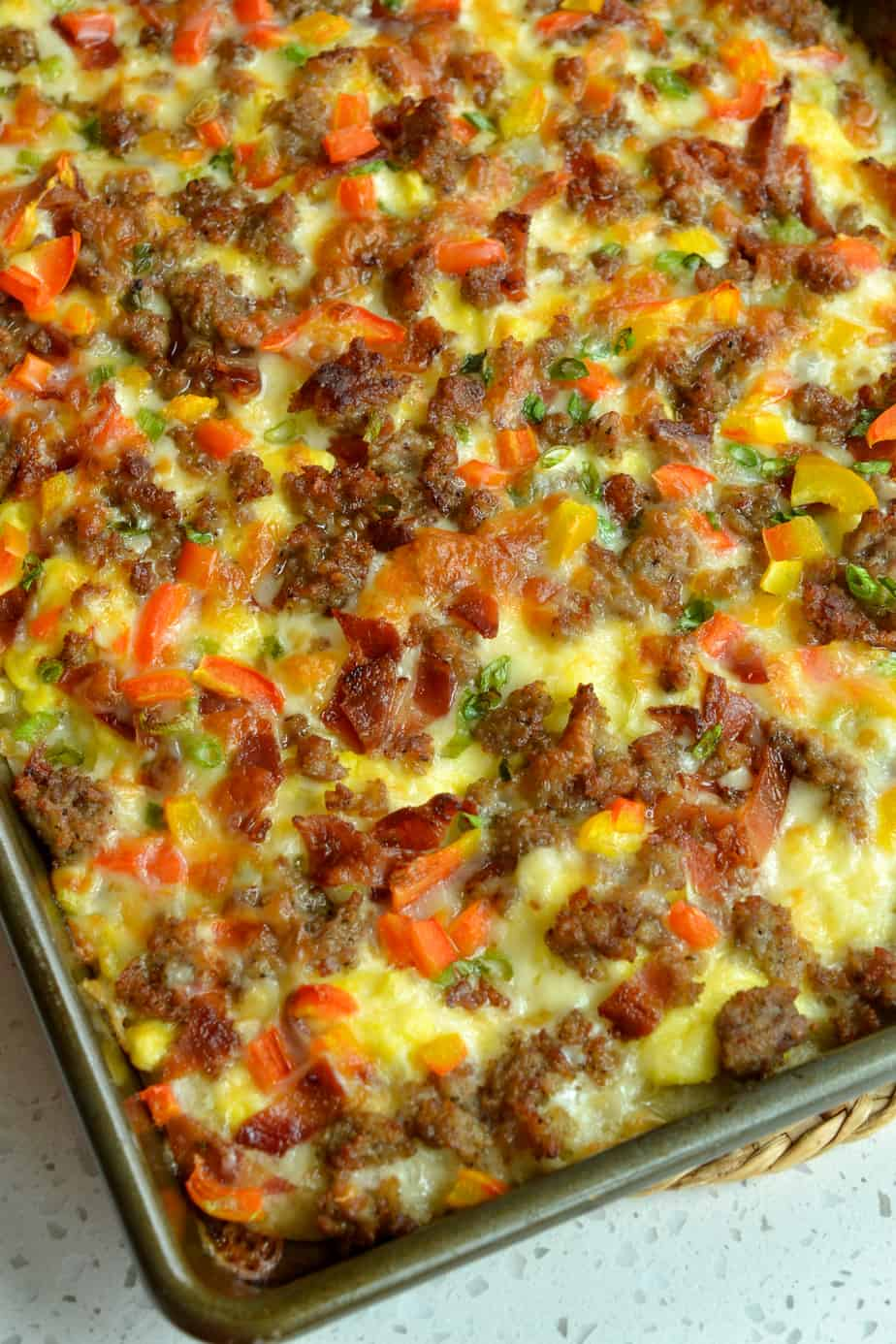 Breakfast Pizza is loaded with crispy bacon, browned pork sausage, sweet red bell pepper, scallions, scrambled eggs and eggs.