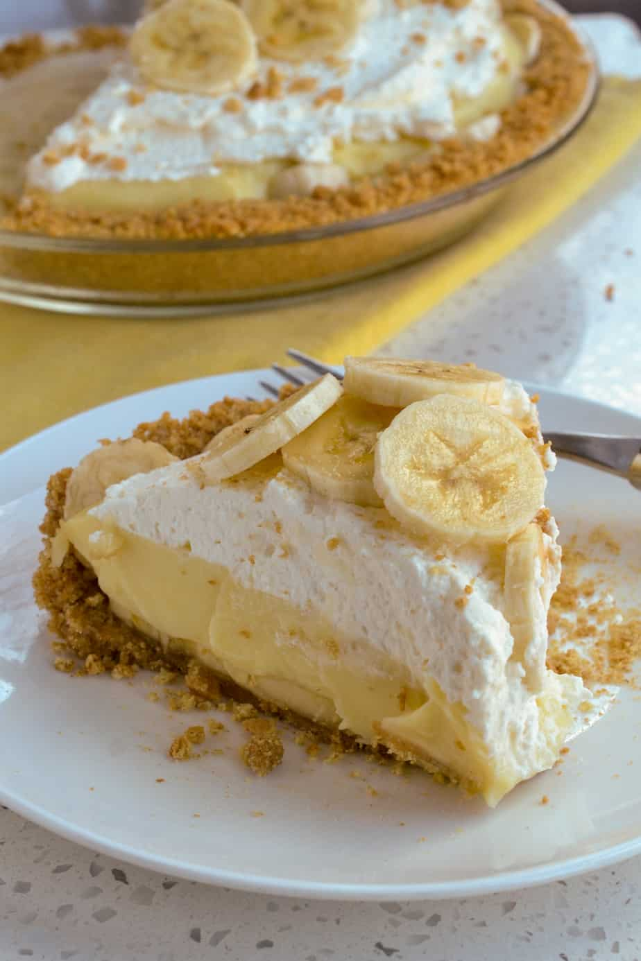 Banana pie topped with fresh whipped cream and banana slices.
