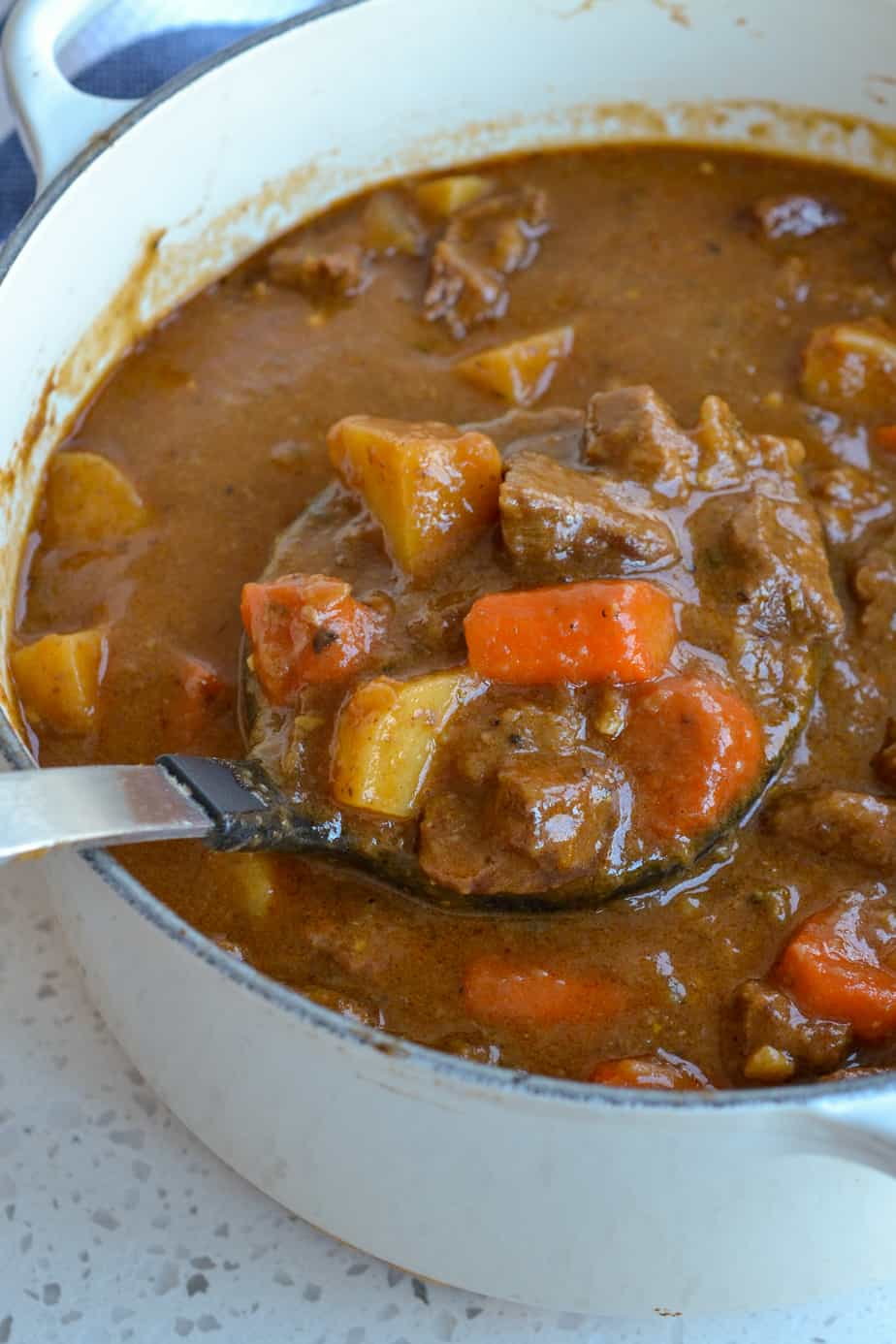 A warm rich and flavorful beef stew with onions, potatoes, and carrots.