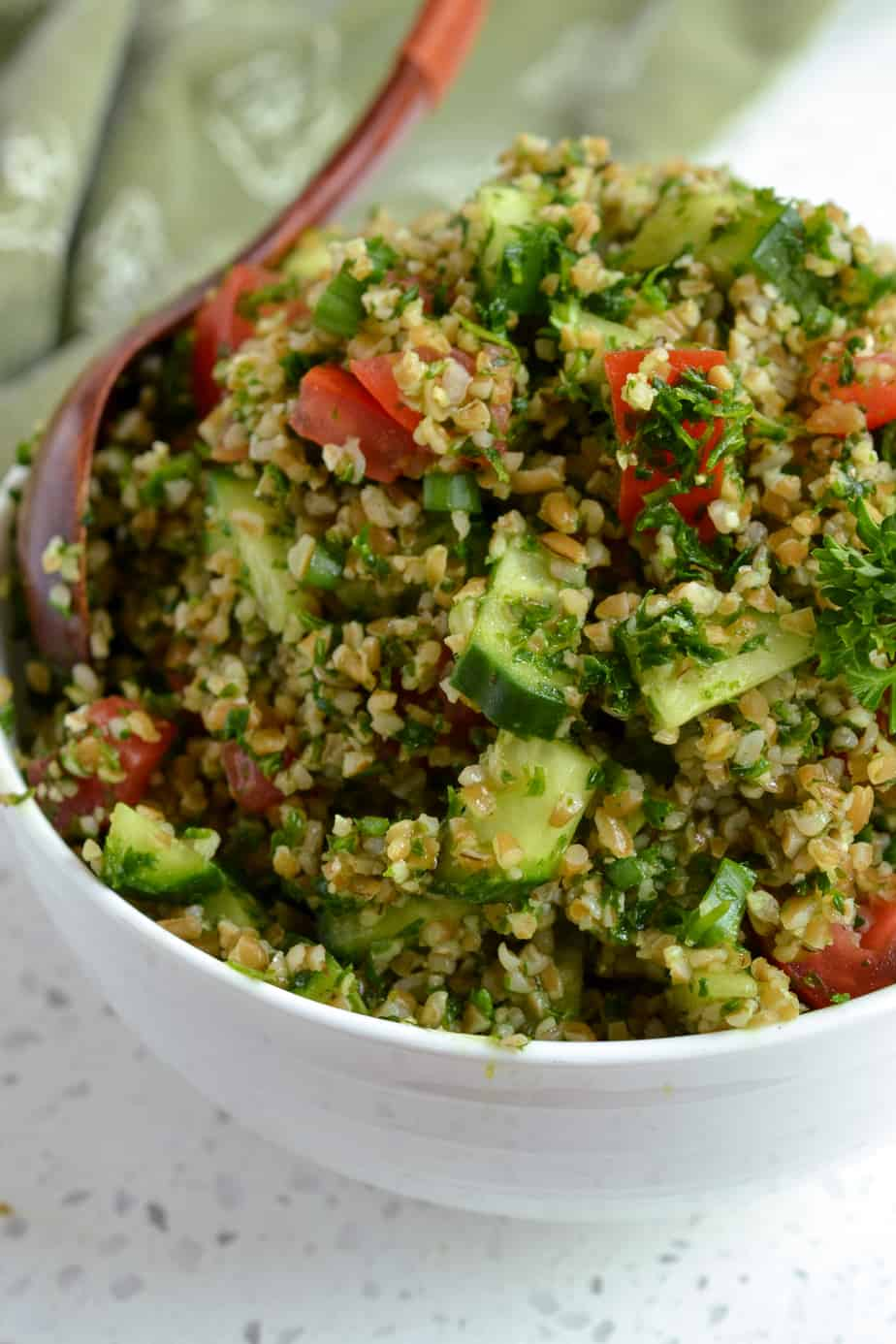 A salad with bulgur wheat, cucumbers, tomatoes, scallions, parsley and mint all drizzled with lemon and olive oil.