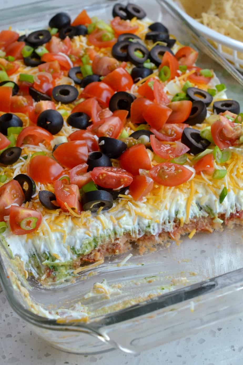 Layered bean dip with avocados and sour cream.