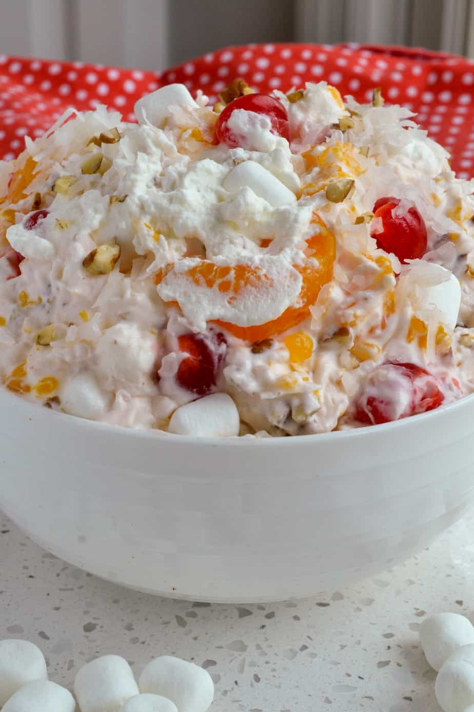 A bowl full of fruit, pecans, coconut, marshmallows, and whipped cream mixed together.