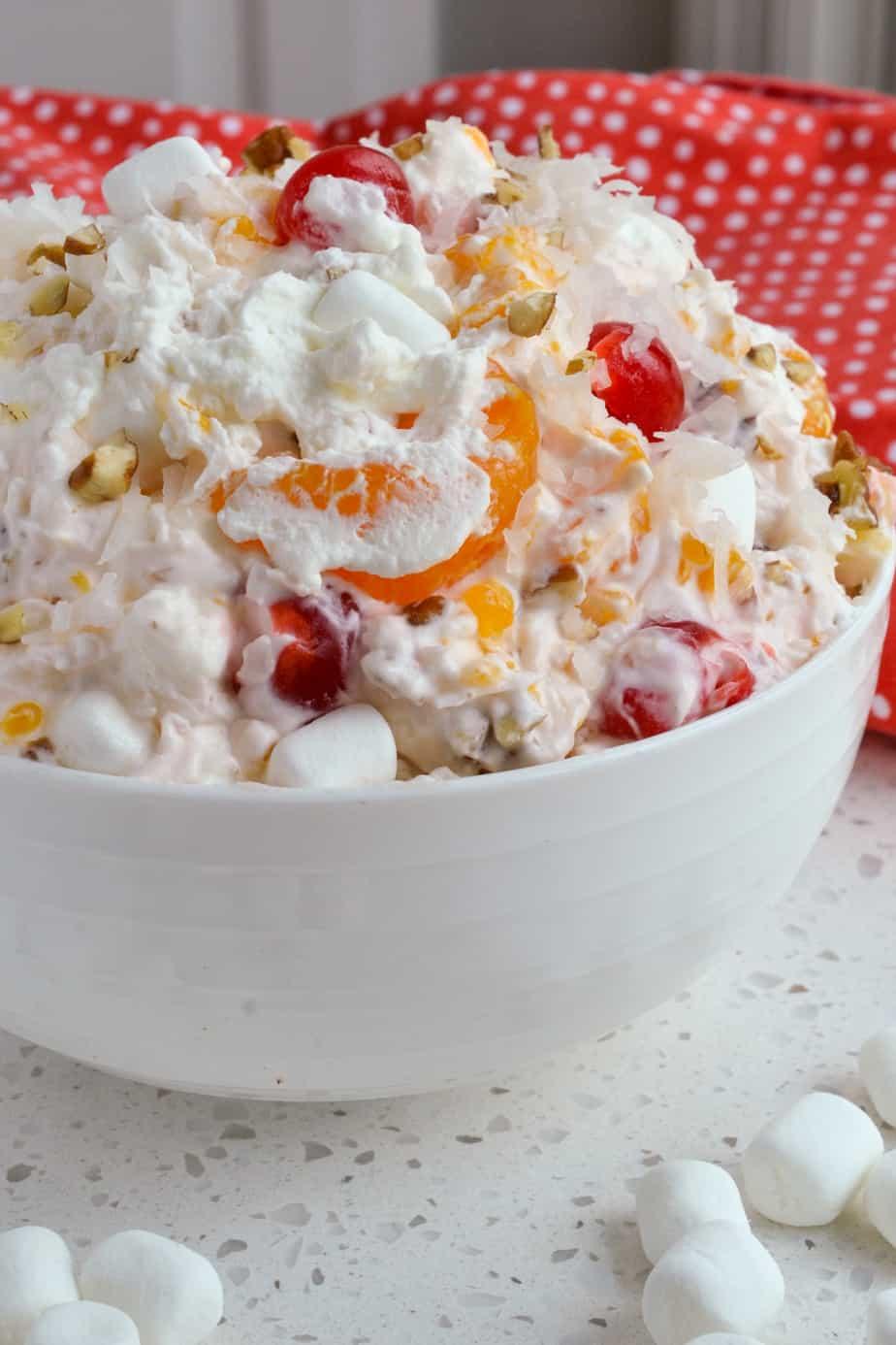 Creamy Ambrosia Salad with cherries, mandarin oranges, and pineapple.