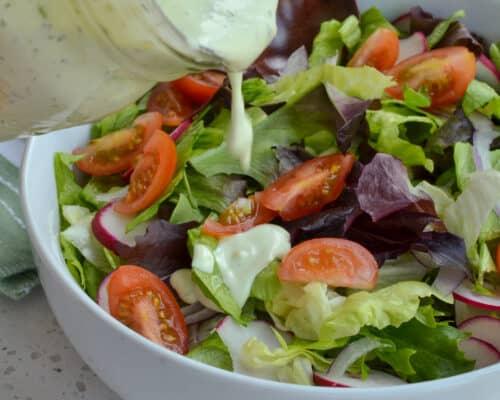 Avocado Ranch Dressing poured on a garden salad