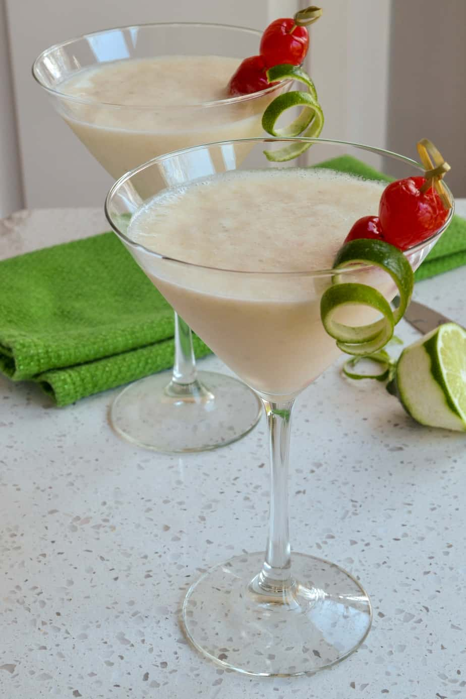 Frozen Banana Daiquiris garnished with a lime twist and a cherry.