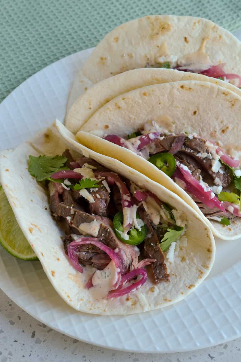 Tortillas filled with grilled steak, pickled onions, and cilantro.