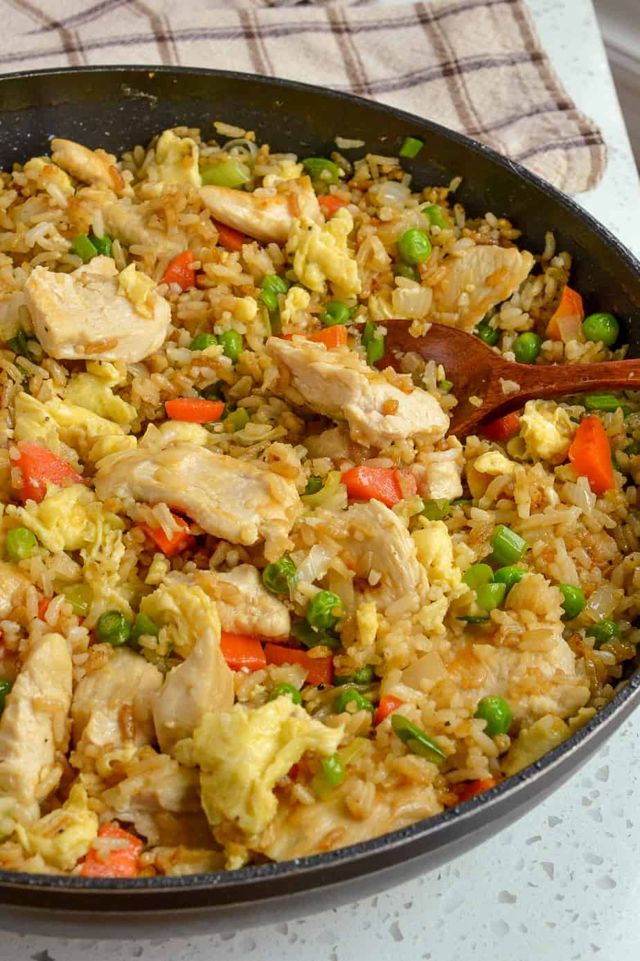 Eggs, chicken, peas, carrots, and green onions in fried rice.