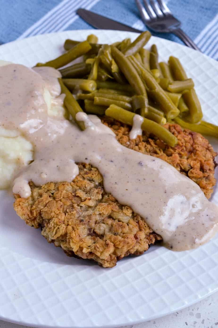 Breaded fried cube steak with mashed potatoes and gravy.