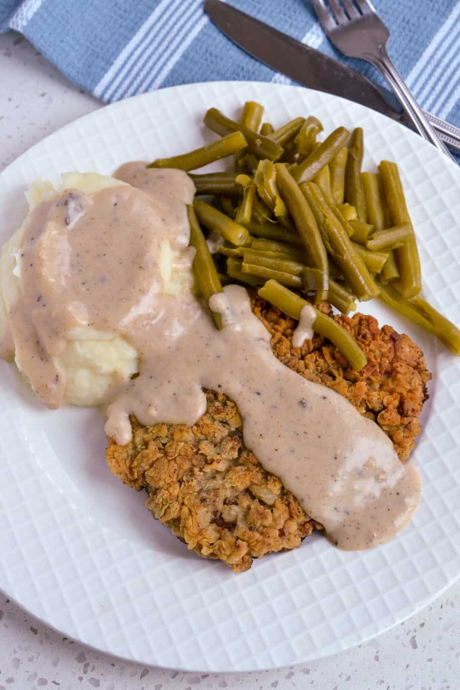Country fried steak with mashed potatoes and green beans